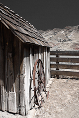 Photo of an an old shed and a wagon wheel